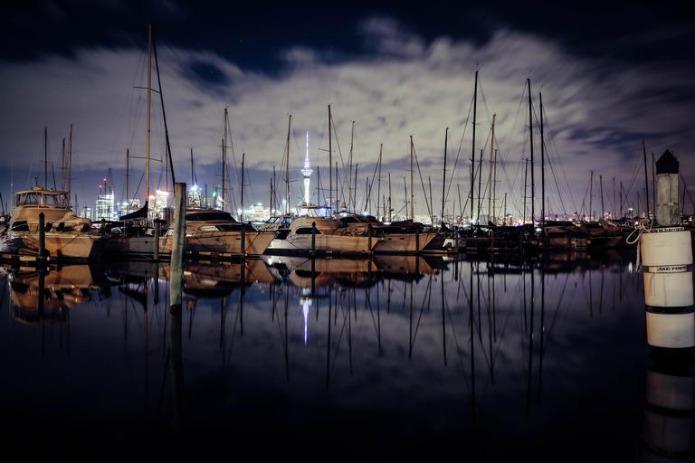 The photograph was taken at Westhaven, Auckland City using Fujifilm xt10 18-55mm lens. The photo is trying to capture the Auckland city by night by emphasizing the sailing boats and the iconic sky tower.