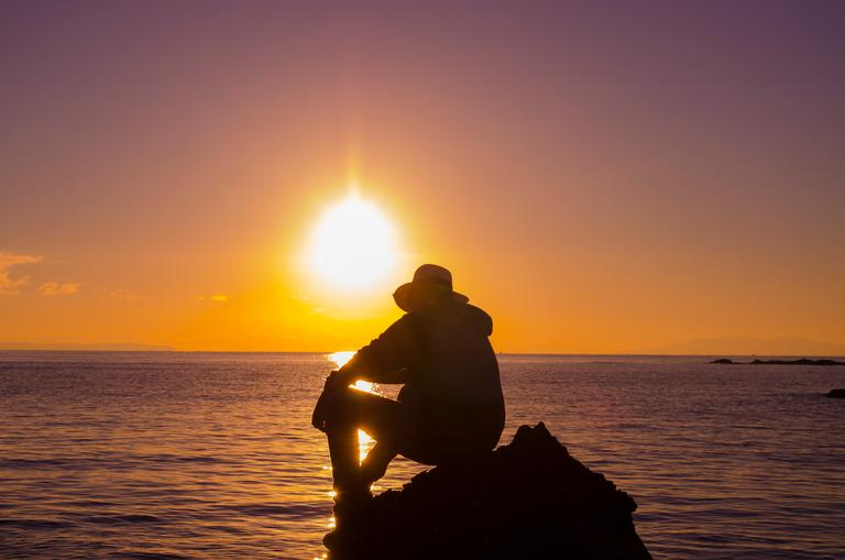 A young man watching the sun rise, as the water slowly engulfs the rock. An inevitable ending...
