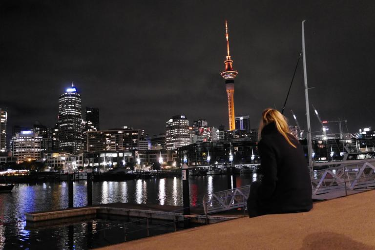 Having a moment of silence while looking at the Skytower, lit up in orange for Matariki Festival celebrating Maori New Year. The picture is also taken to capture the matching contrast between tower, hair and ground to create a connection.